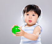 Baby hold plastic ball with headphone — Stock Photo