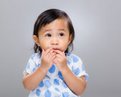 Little girl put finger into mouth — Stock Photo