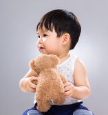 Adorable baby boy play with doll bear — Stock Photo