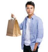 Asian man carry paper bag — Stock Photo
