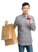 Man hold shopping bag and credit card — Stock Photo