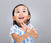Little girl clap hand and look up — Stock Photo