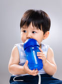Baby boy drink with water bottle and look away — Foto de Stock