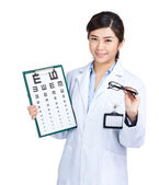 Optician doctor with eye chart and glasses — Stock Photo