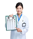Asian doctor with eye chart — Stock Photo