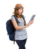 Woman with backpack look at digital tablet — Stock Photo