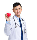 Male doctor with heart shape ball — Stock Photo