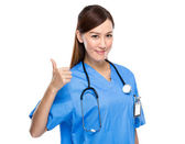 Young female doctor thumb up on white background — Stockfoto