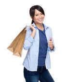 女性の買い物袋の親指をホールド アップ — ストック写真