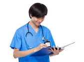 Asian young medical doctor take note on clipboard — Stock Photo
