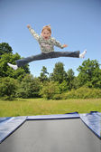 The young gymnast carries out jumps on a trampoline — Stock Photo