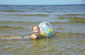 The girl bathes with a ball in water, at seacoast in Jurmala (La — 图库照片