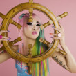 Young woman holding ship's wheel in front of her face — Stock Photo #21783853
