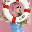 Stock Photo: Young woman holding float tube over pink background