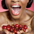 Cheerful young woman looking at cherry in her hands - Stock Photo