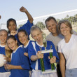 Female Soccer Player With Friends And Parents Holding Trophy - Stock Photo