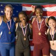 Multiethnic excited female athletes with American flag and medals — Stock Photo