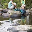 Friends Relaxing By Stream — Stock Photo