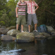 Friends Standing On Stones By River — Stock Photo #21786865
