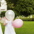 Girls Holding Balloons In Garden — Stock Photo #21787879