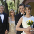 Bride And Groom With Parents In Background — Stock Photo