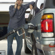 Man Pumping Gas Into Car - Stock Photo