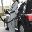 Stock Photo: BusinesswomRefueling Car At Station