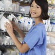 Female Pharmacist Standing By Shelf — Stock Photo