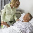 Woman Visiting Man In Hospital - Stock Photo