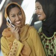 Two Muslim Women One Using cell Phone — Stock Photo