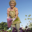 Happy Senior Woman Watering Plants — Stock Photo