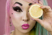 Woman holding slice of lemon in front of her eyes — Stock Photo