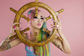 Young woman holding ship's wheel in front of her face — Stock Photo