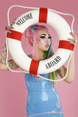 Young woman holding float tube over pink background — Stock Photo