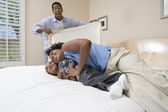 Woman playing with son on bed — Stock Photo