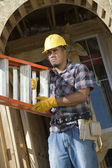 Worker carrying stepladder — Stock Photo