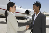 Business Colleagues Shaking Hands At Airfield — Stock Photo