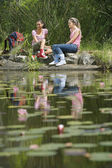 Female Hikers Resting By The Pond — Stock Photo