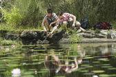 мальчики-подростки на корточках у озера — Стоковое фото