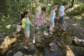 Friends Crossing Stream While Holding Hands — Stock Photo