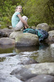 Young Girl Sitting On Stones By Forest Stream — Stock Photo