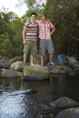 Friends Standing On Stones By River — Stock Photo