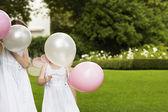 Girls Holding Balloons In Garden — Stock Photo