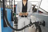 Mujer contando dinero en estación de combustible — Foto de Stock