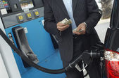 Businessman Counting Money At Fuel Station — Stock Photo