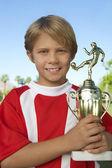 Jeune garçon tenant le trophée de football — Photo