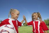 Flickor ger en high-five på fotbollsplan — Stockfoto