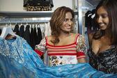 Seleccionar un vestido en la tienda de mujeres — Foto de Stock