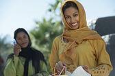 Mujer india con amiga llamada en segundo plano — Foto de Stock
