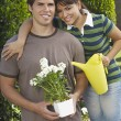 Couple Holding Watering Can And Flower Pot — Stock Photo #21790175